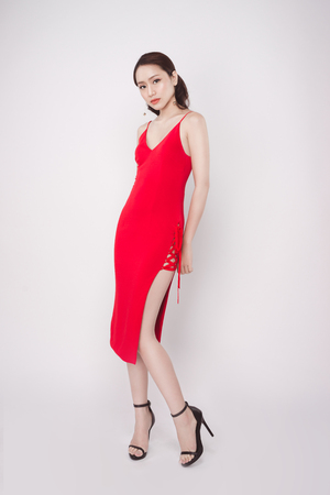 Beautiful stylish asian woman wearing red dress on grey background. Фото со стока