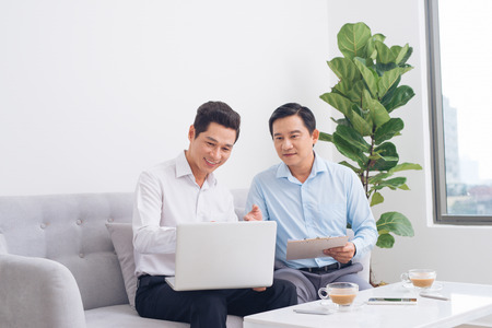 Two confident young businesspeople using a laptop discuss information while sitting on a sofa in a modern office Stock Photo