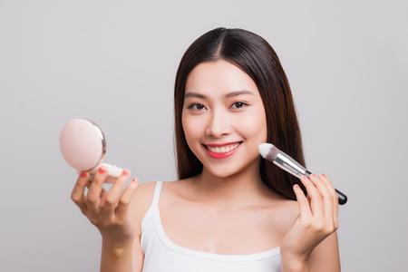 Belle jeune femme asiatique tenant une boîte de fondation et une brosse