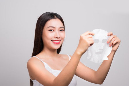 Beautiful asian woman applying paper sheet mask on her face white background. Stockfoto