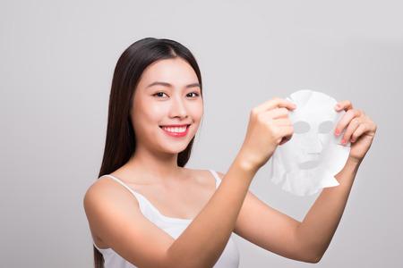Beautiful asian woman applying paper sheet mask on her face white background. Standard-Bild