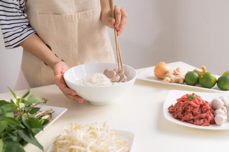 女性シェフは、ハーブ、肉、米麺と伝統的なベトナムのスープフォーボーを準備します 写真素材