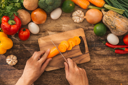Cutting carrot. Male hands cooking vegetables salad in kitchen. Top view.