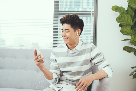 Smiling asian handsome man sitting on cosy sofa listening to music Stockfoto