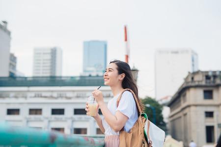 Junges schönes Mädchen, das auf einer Brücke mit Stadtansicht mit Kaffeetasse in ihrer Hand steht. Standard-Bild - 97281082