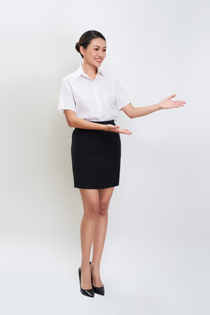 Full body portrait of happy smiling young beautiful business woman showing something or copyspase
