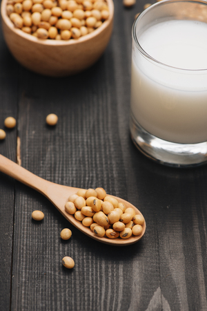 Glass with soy milk and soy bean on wooden background Stock Photo