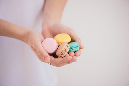 Sweet dessert. Colorful macarons on female hands. 写真素材