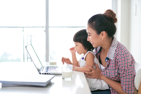Asian mother woman with a her daughter working at the computer