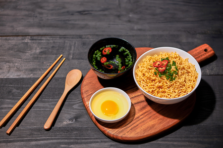Instant noodles with egg in wooden bowls