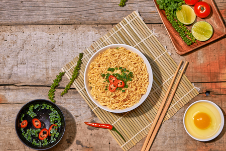 instant noodles in bowl with vegetable on wooden table.