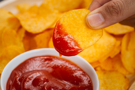 Potato chips and ketchup. Beer snack, unhealthy eating Stock Photo