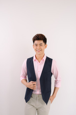 Handsome asian man stand and smile posing on gray background 스톡 콘텐츠