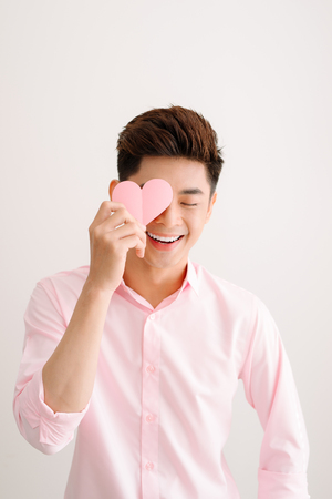 Handsome asian man holding pink heart paper posing on gray background Stok Fotoğraf