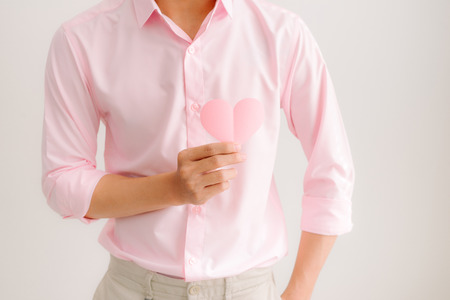 Handsome asian man holding pink heart paper posing on gray background 版權商用圖片