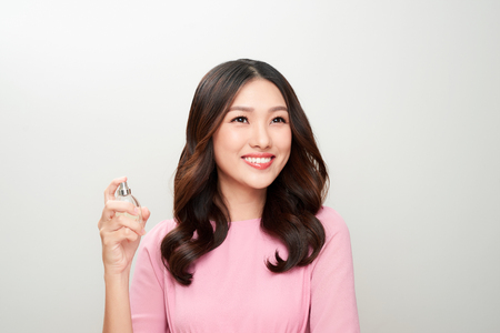 Beautiful asian woman holding a perfume bottle and applying it Stock fotó