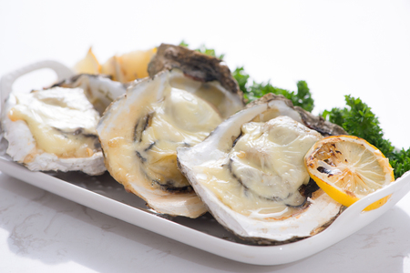 Fresh opened oysters on a white plate. Selective focus