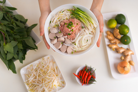 Female chef prepare traditional Vietnamese soup Pho bo with herbs, meat, rice noodles Stok Fotoğraf - 97609277