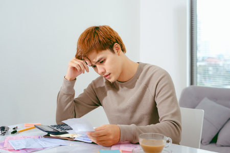 Asian man doing finances and calculate about cost at home office. 免版税图像