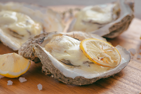 Open shell oyster with lemon and salt on a wooden board Archivio Fotografico - 97766380