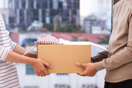 De mens die een boek en de kleren houden schenkt doos. Donatie concept. Stockfoto