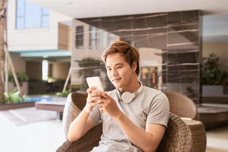 Summer sunny day, cheerful attractive smile asian man uses the smartphone Banco de Imagens