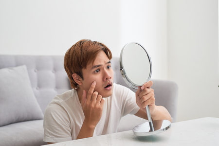 Handsome man looking at himself in mirror. Squeezing pimple. Banque d'images
