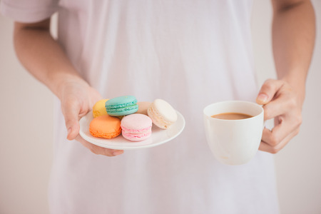 Hands holding colorful pastel cake macarons or macaroons 写真素材 - 98307617
