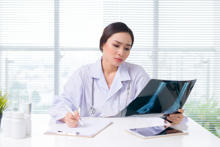Medical asian doctor working with hologram interface at hospital