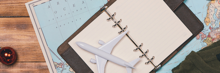 travel , trip vacation, tourism mockup - close up of clothes, christmas decorations and toy airplane and touristic map on wooden table. Banner size.