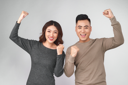 Smiling happy asian couple holding both thumbs up Stockfoto