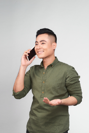 Portrait of a cheerful young asian man on call against grey background