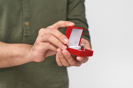 Close up of male hands holding wedding ring and gift box. Stock Photo