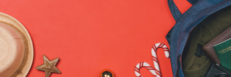 HOLIDAY travel concept - passport, camera, hat, airplane, chrismas decorations on red background. Banner size.
