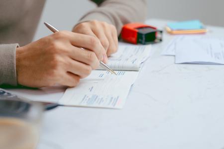 Bemannen Sie das Schreiben eines Zahlungsschecks am Tisch mit Taschenrechner und Stempel
