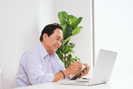 Senior man working with laptop and basic things for work at his desk