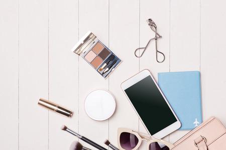 カメラとパスポートを持つテーブルの上の女性化粧品やファッションアイテム。トップ ビュー