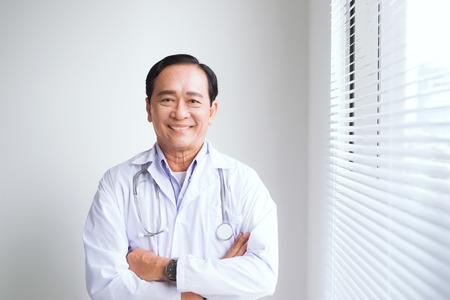 Portrait of senior doctor standing in medical office