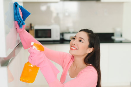 Beautiful asian woman in protective gloves cleaning kitchen cabinet