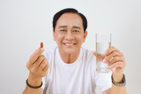 Elderly ill man with vitamin  omega 3 in hands.