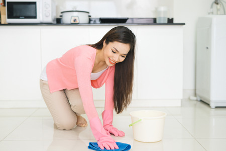 Happy asian woman cleans floor in the kitchen