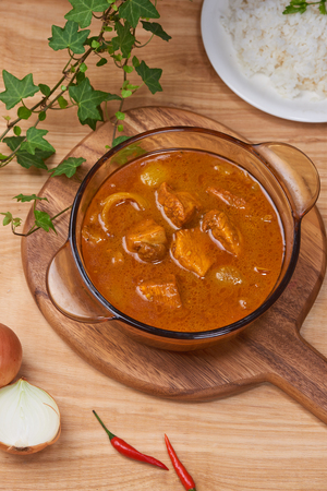 Chicken curry with spice in pot on wooden background Foto de archivo - 98716124