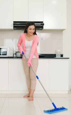 Home cleaning service woman with mop cleaning floor in the kitchen Фото со стока