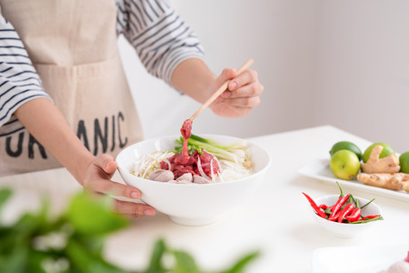 Female chef prepare traditional Vietnamese soup Pho bo with herbs, meat, rice noodles Stok Fotoğraf - 99234496