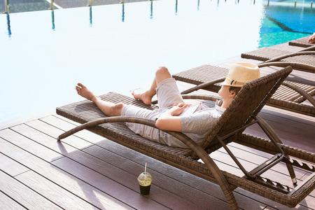 Momentos de pereza. Chico asiático durmiendo en la piscina del sofá en verano