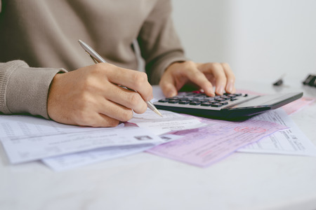 Hand man doing finances and calculate on desk about cost at home office.