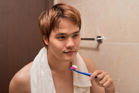 Brushing teeth in the morning.  Attractive young man brushing teeth with toothbrush, looking at himself in mirror