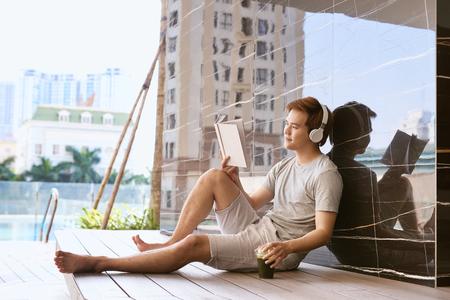 Joven asiático leyendo un libro y escuchando música junto a la piscina en un día soleado de verano