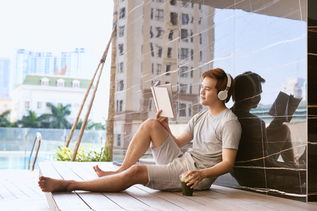 Junger asiatischer Mann, der Buch liest und Musik durch den Pool an einem sonnigen Sommertag hört