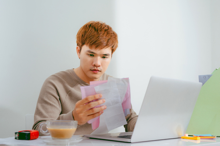 Young sad man analyzing home finances while gesturing with hand and looking at documents. Sitting near table with tablet.